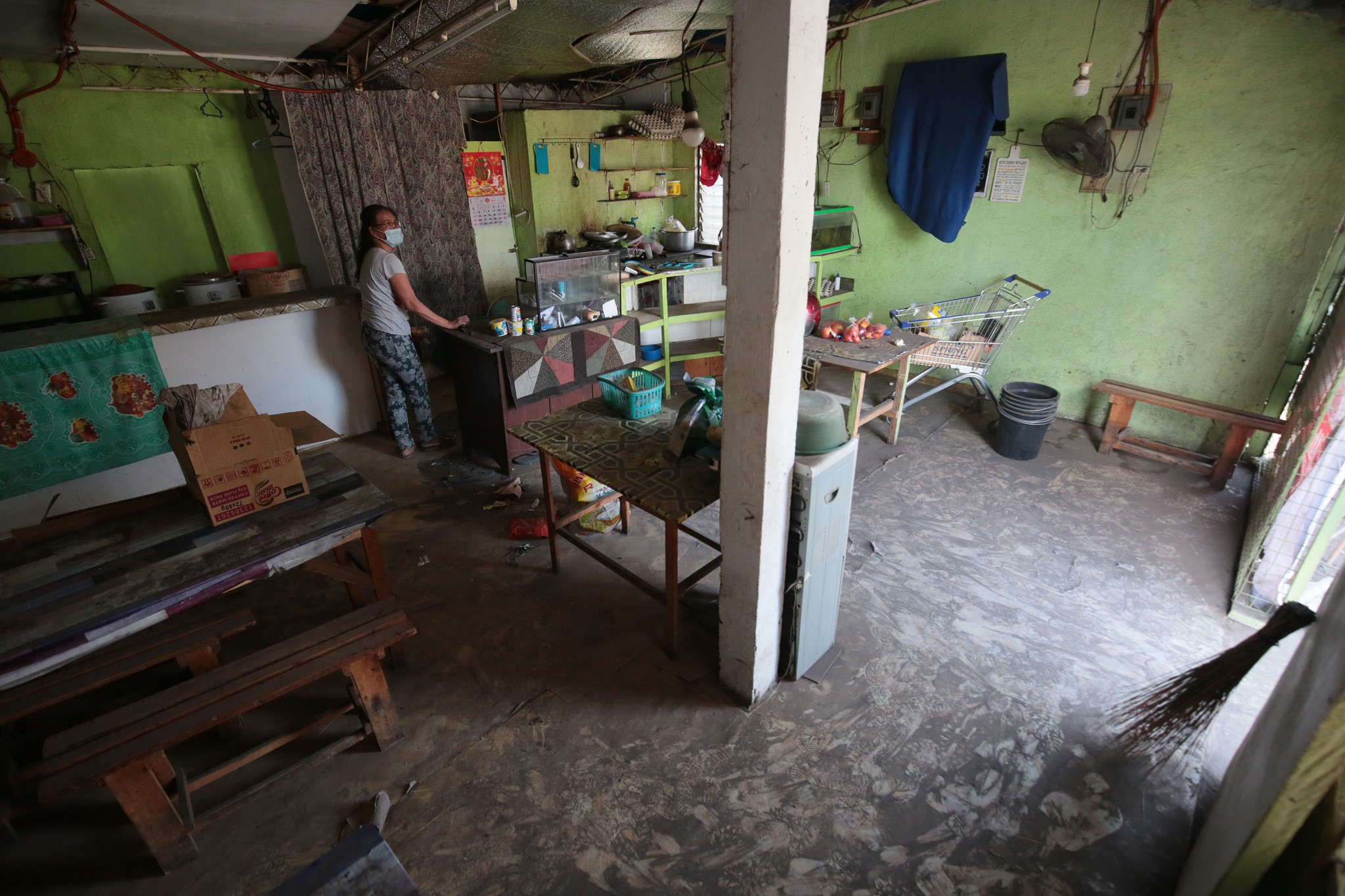 A Lemery resident cleans up her home after being allowed to return two weeks following Taal Volcano erupted last January 12.